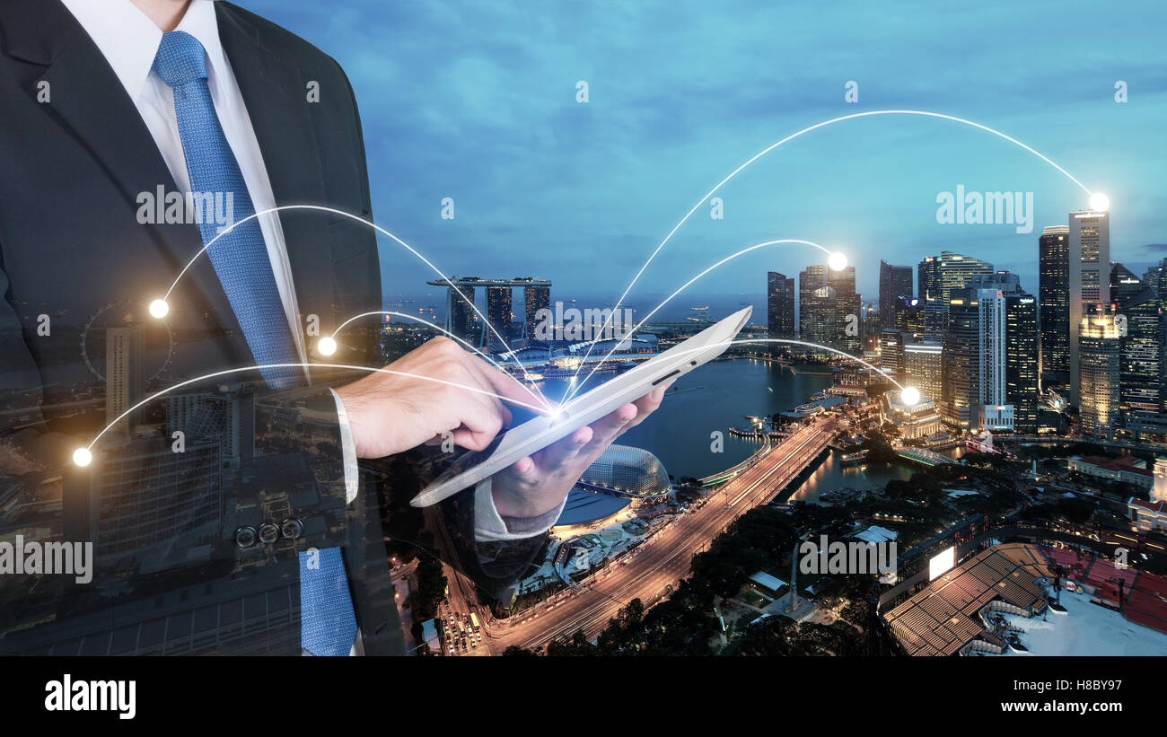 Double exposure of businessman using digital tablet pc with network connection of Singapore city. Network connection - Stock Image