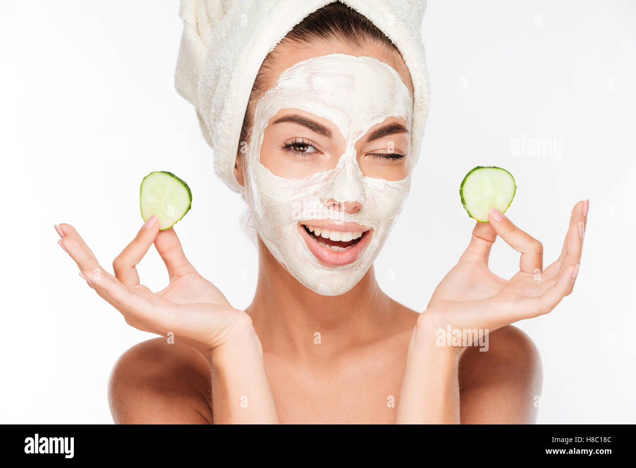 Young woman with clay facial mask holding cucumber slices isolated on white background - Stock Image