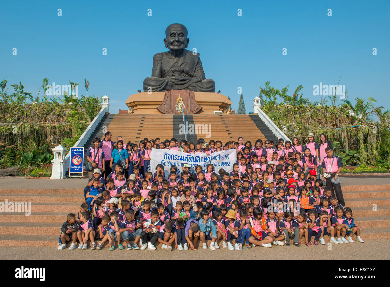 Thai school children having a group photo in front of the iconic sculpture of revered Buddhist monk Luang Pu Thuat - Stock Image