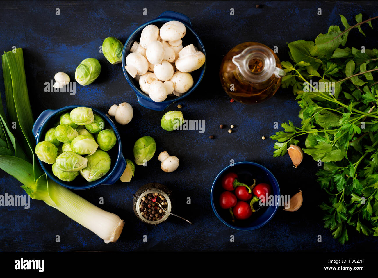 Dietary menu. Ingredients: Vegetables - Brussels sprouts, mushrooms, leeks and herbs on a dark background. Top view. - Stock Image