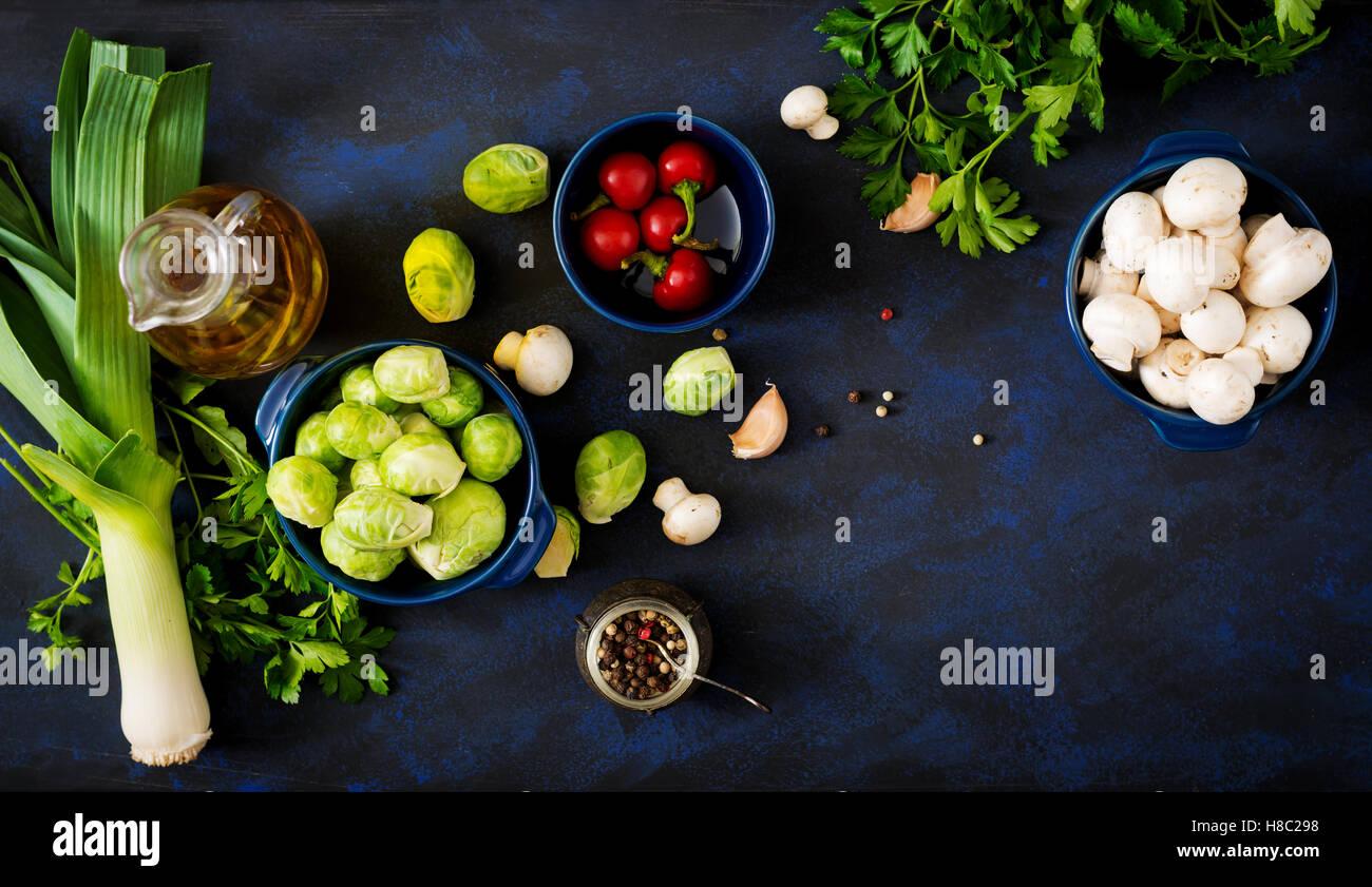 Dietary menu. Ingredients: Vegetables - Brussels sprouts, mushrooms, leeks and herbs on a dark background. Top view. - Stock Image