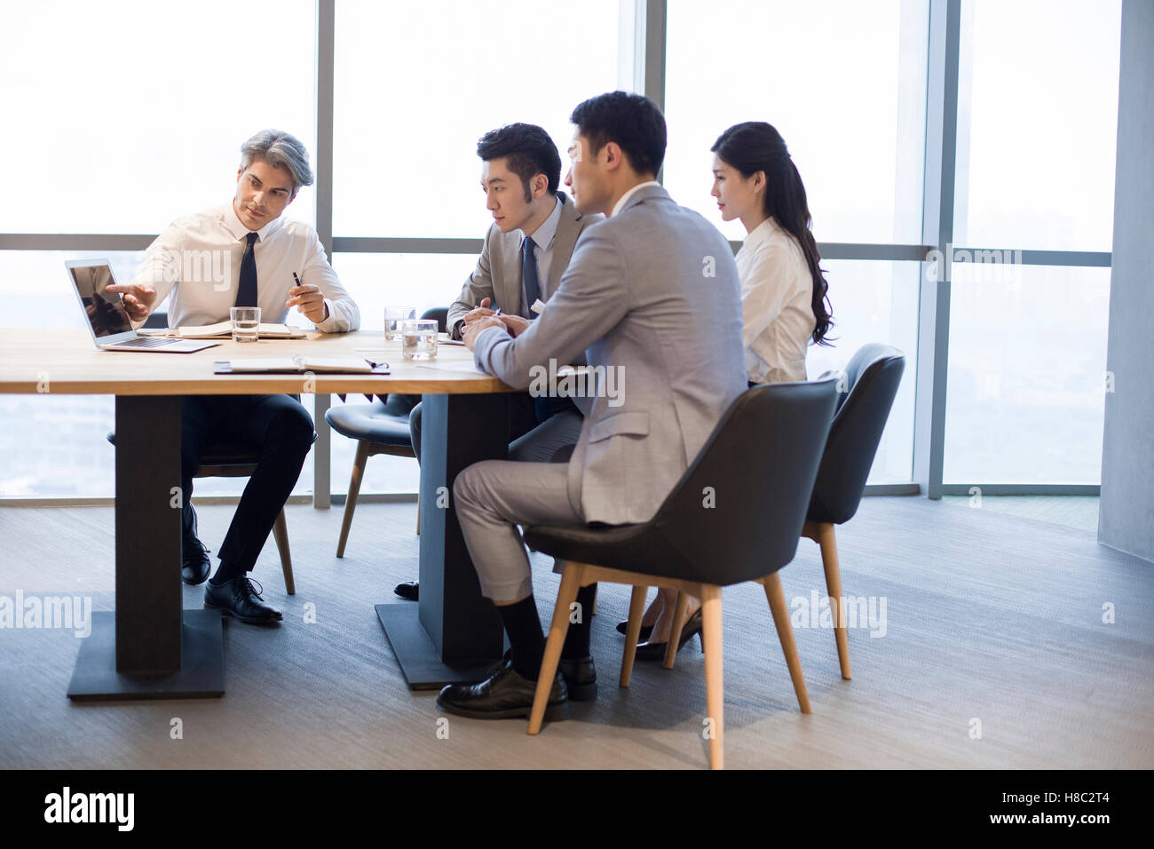 Chinese business people having meeting in board room - Stock Image