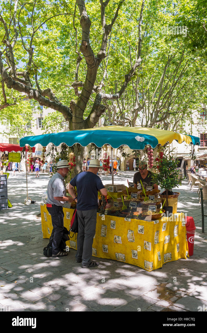 People at a local produce market stall in Place aux Herbes in medieval Uzès, Gard, France - Stock Image