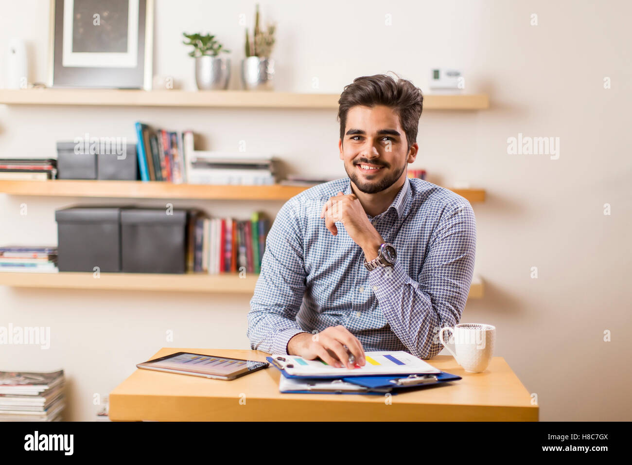 Young freelancer analyzes statistical report at the desk Stock Photo