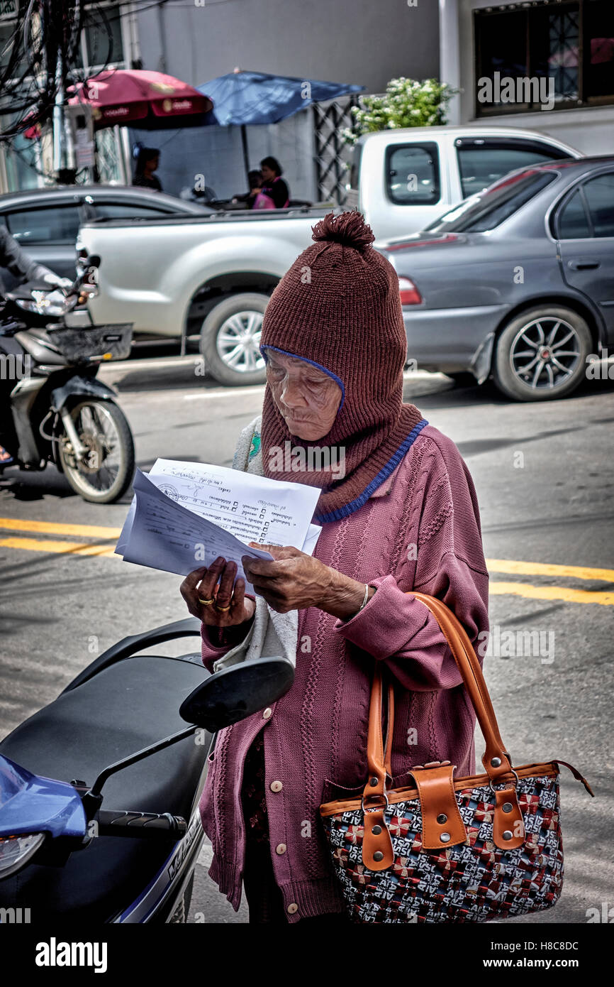 Elderly Thailand woman with payment demand notice. S. E. Asia - Stock Image