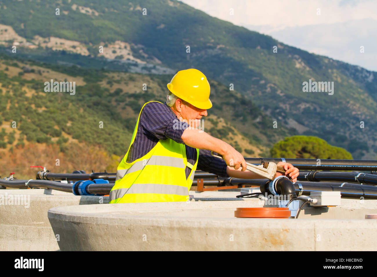 plumber at work in a building site - Stock Image