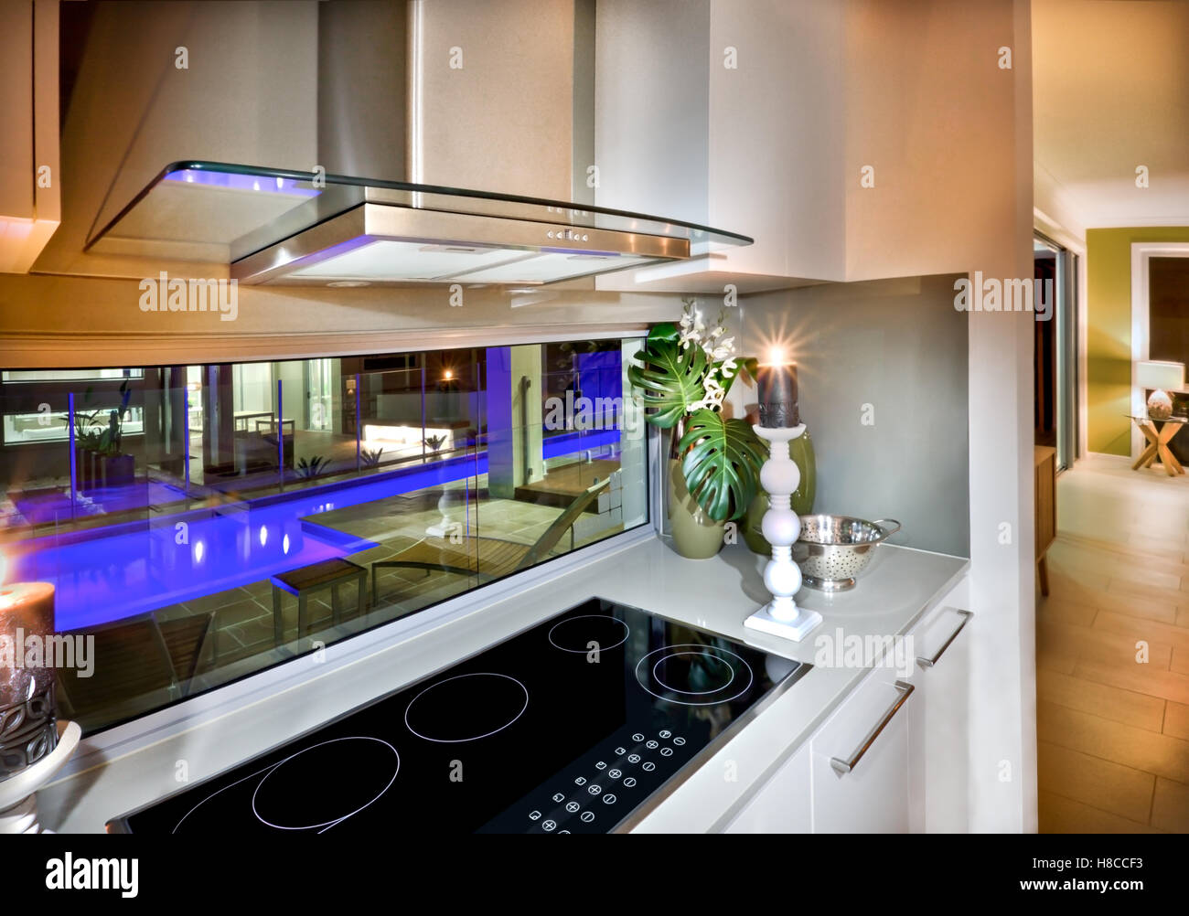 Black color stove included modern technology installed on white counter top with flashing candles from both sides. - Stock Image