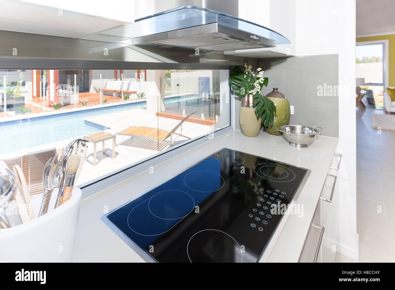 Modern stove with ceramic tech besides spoons near the window in the kitchen, view of swimming pool through the - Stock Image