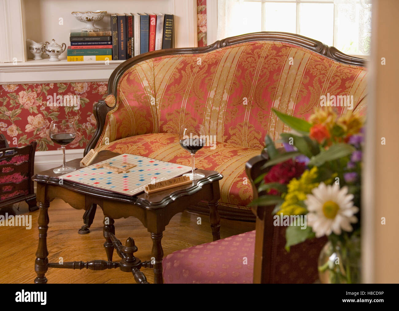 Wood framed sofa with red upholstery, game of scrabble and two glasses of red wine on small table. - Stock Image