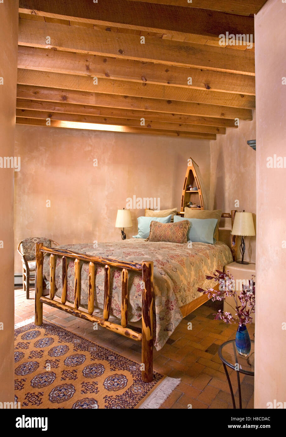 Wood framed bed in rustic, country bedroom with timber framed roof and adobe walls, Santa Fe, New Mexico. - Stock Image