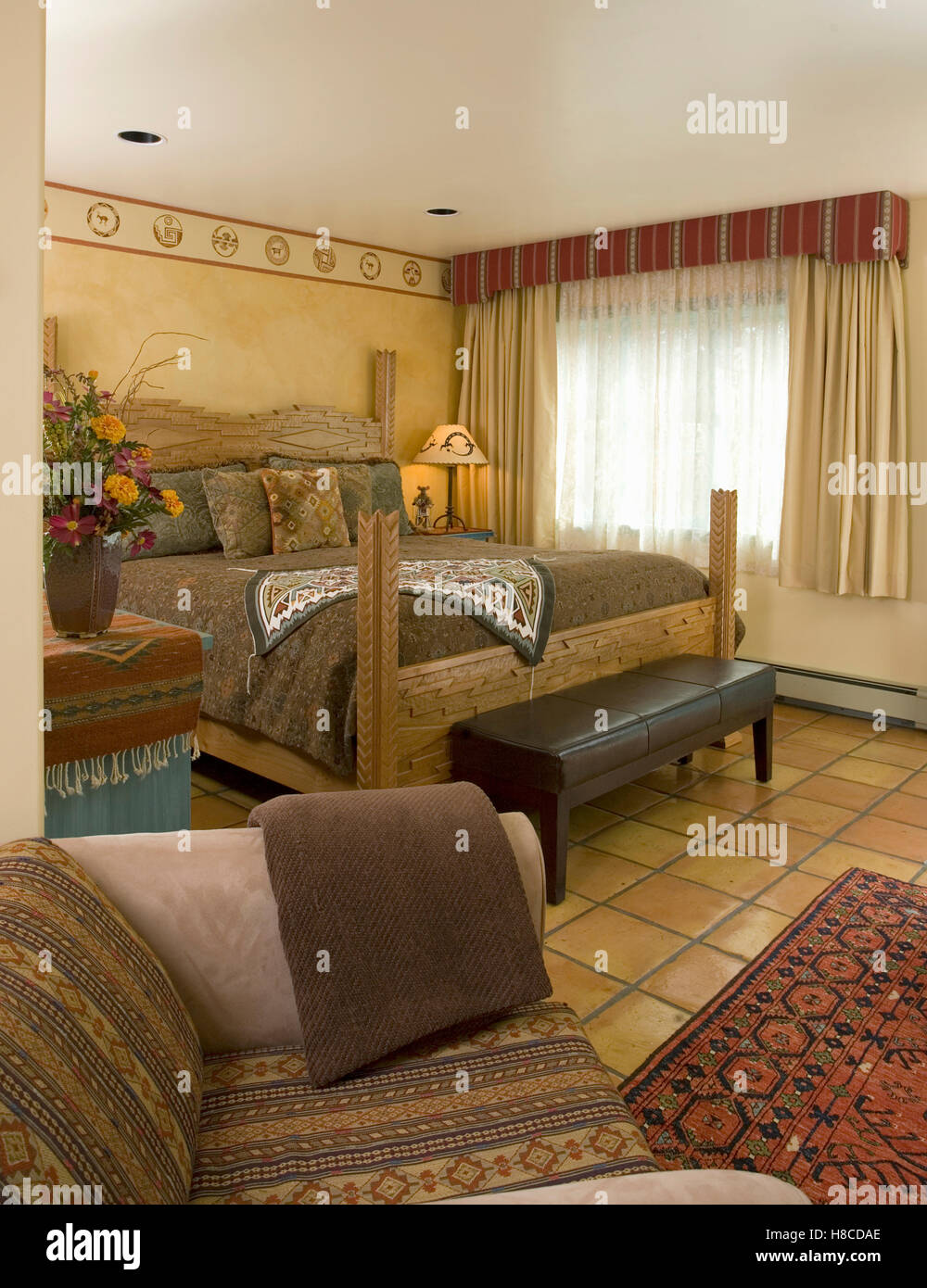 Wood framed bed by window in bedroom with tiled floor, Santa Fe, New Mexico. - Stock Image