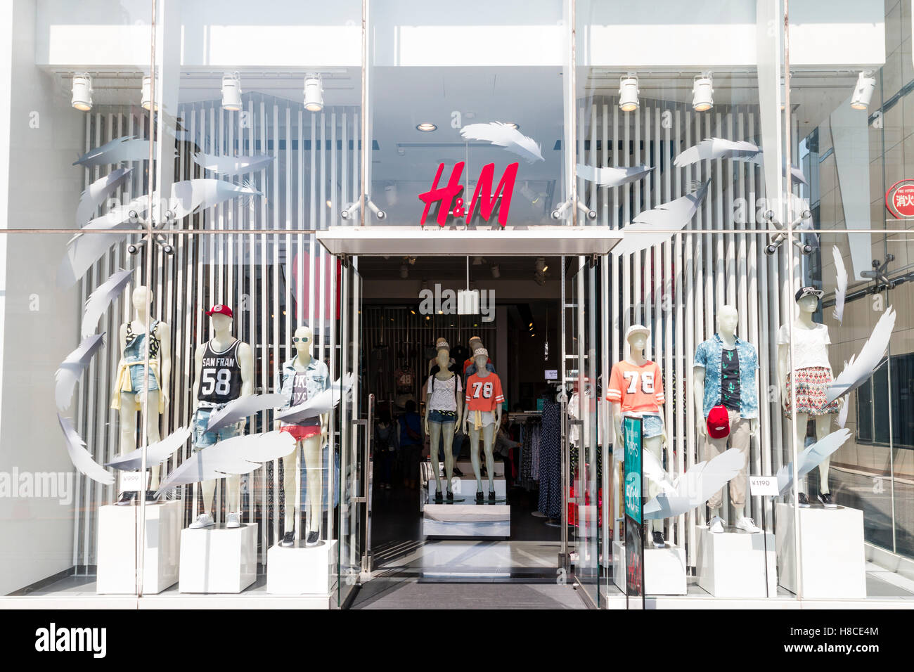 Japan, Tokyo, Harajuku. Fashionable H&M chain clothing store entrance and store front, with white feathers theme - Stock Image