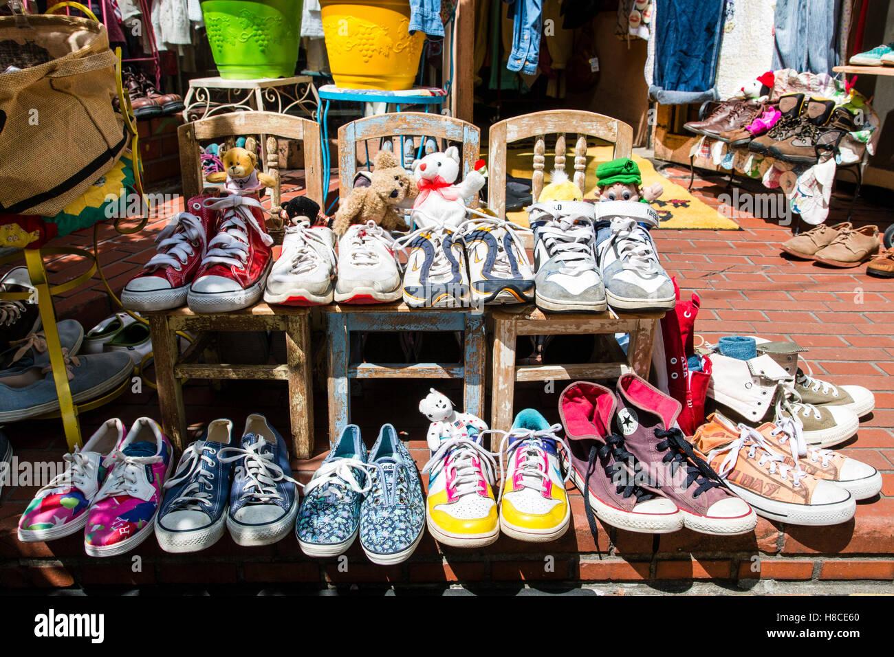 Japan, Tokyo, Harajuku, Takeshita-dori. Panama Boy used, 2nd hand store. Outside entrance, display of trainers arranged - Stock Image