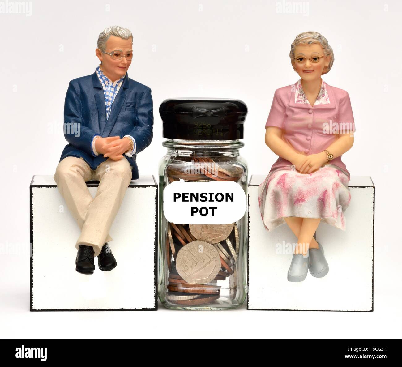 Two pensioner figurines with a pension pot money jar. - Stock Image