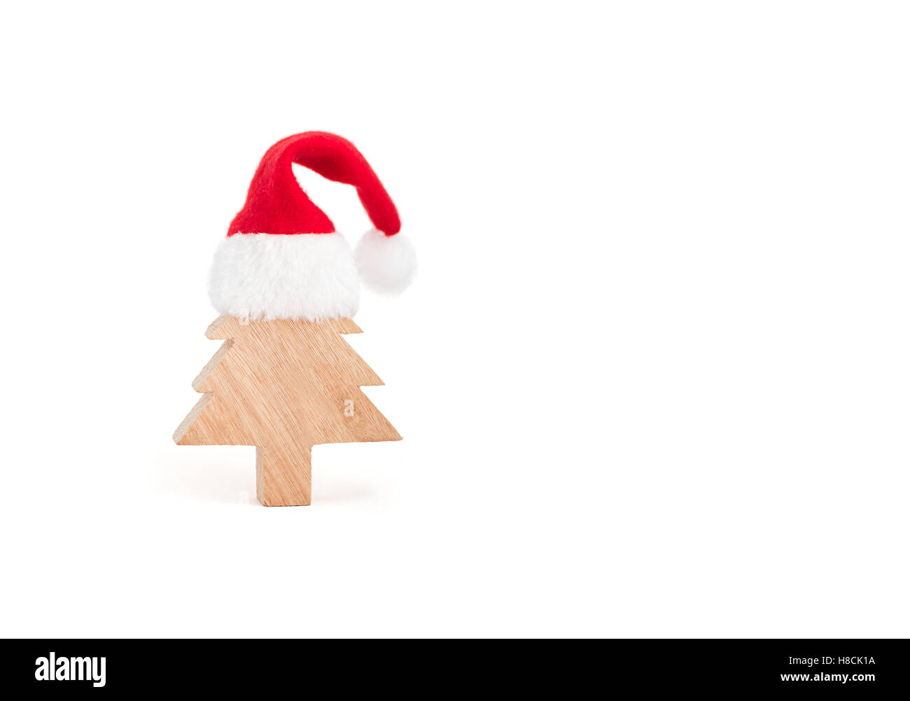 1a3df9f6adfe1 A handmade wooden christmas tree wearing a tiny red christmas hat on white  background. Silly