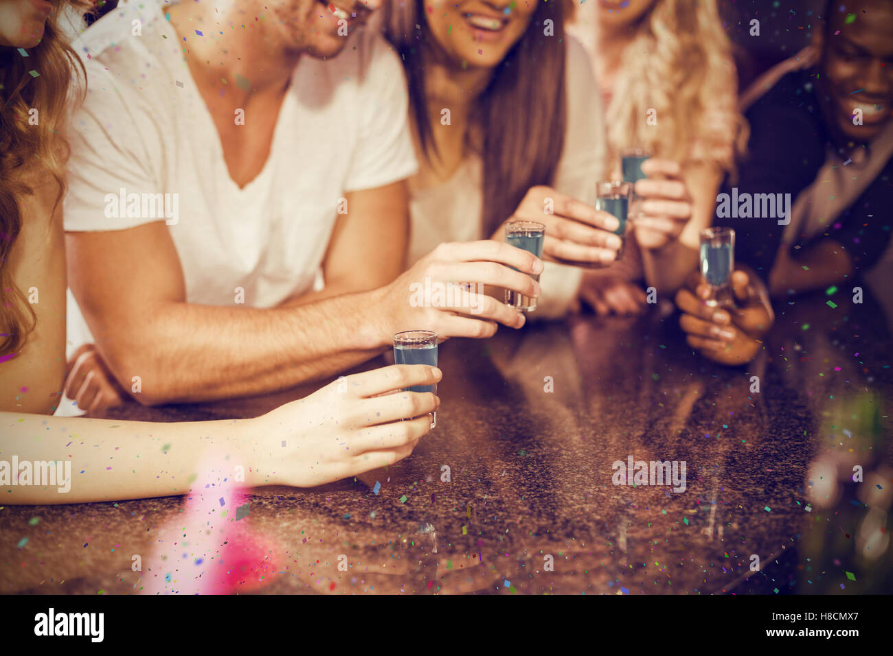 Composite image of cropped image of hands having shots - Stock Image