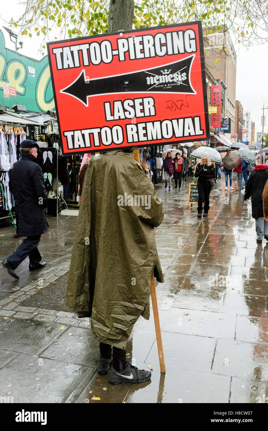 Person holding sign advertising tattoo, piercing and tattoo removal services, Camden High street, London, UK. - Stock Image