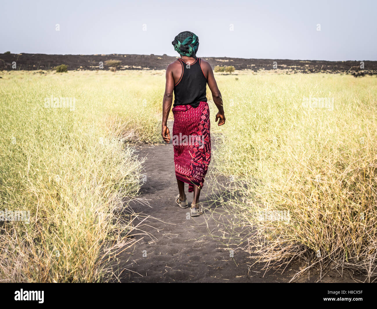 Local tourist guide leading a group down from Erta Ale active volcano in Afar Region in Ethiopia, Africa. - Stock Image
