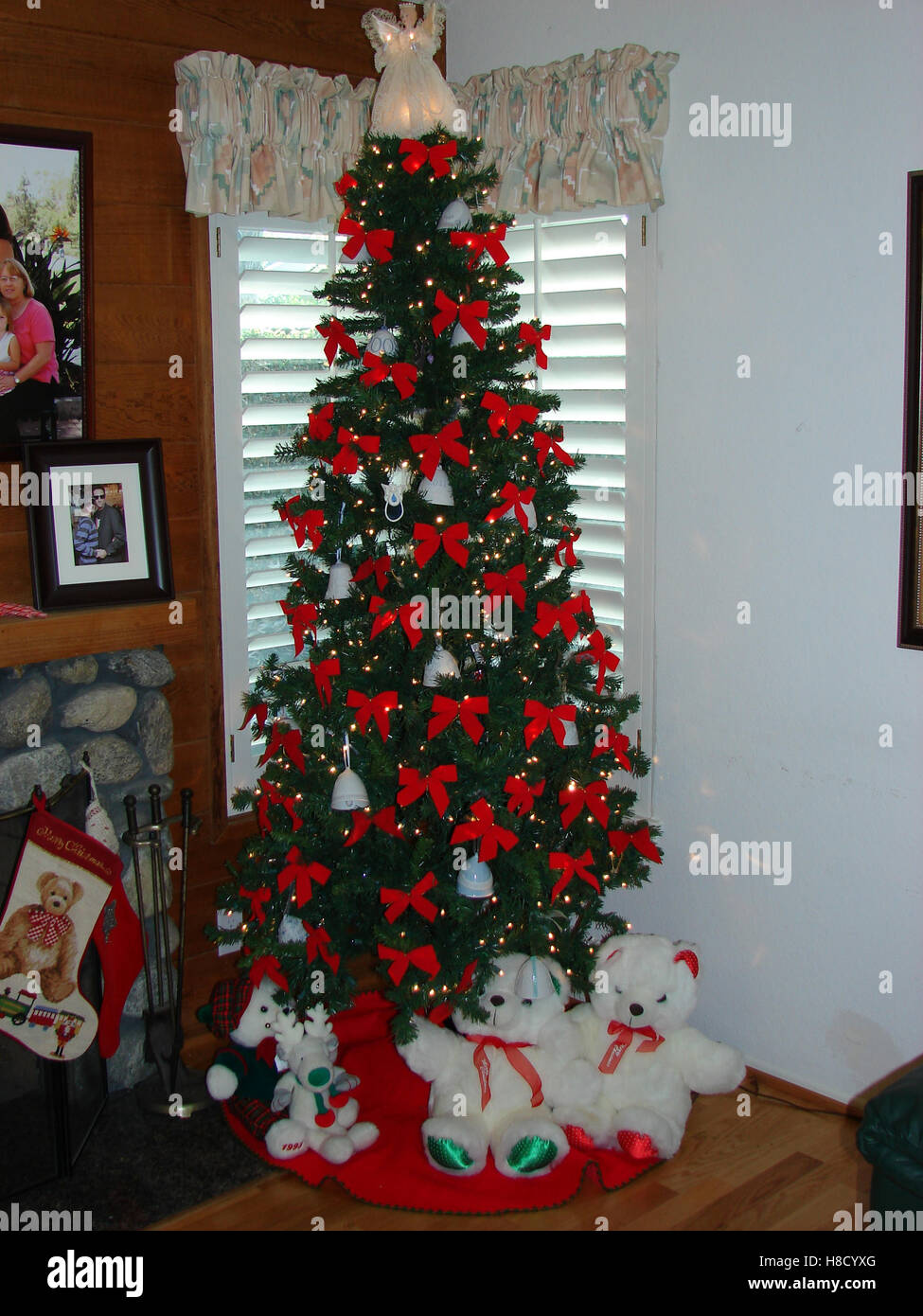Christmas Tree with bright red bows and stuffed animals around it - Stock Image