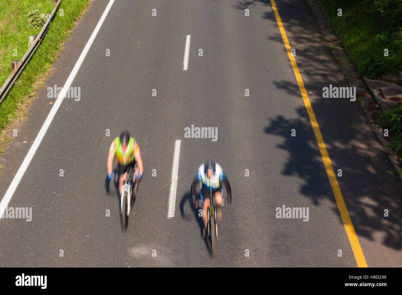Cycling cyclists racing speed blur overhead photo action on road - Stock Image