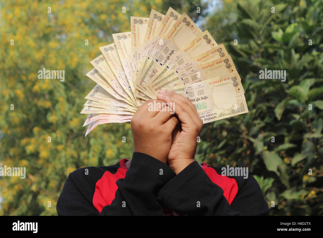 A unidentified boy took some Indian currency in the air. Now these currencies are invalid. Waiting for rebirth. - Stock Image