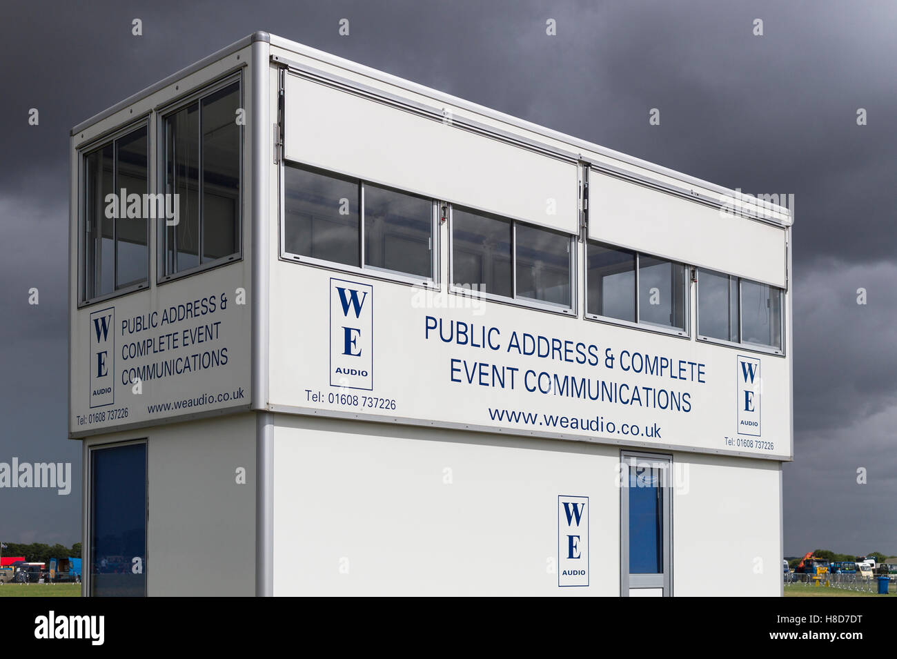 Operations cabin for on-site event public address service at an English show under a storm-threatening sky - Stock Image