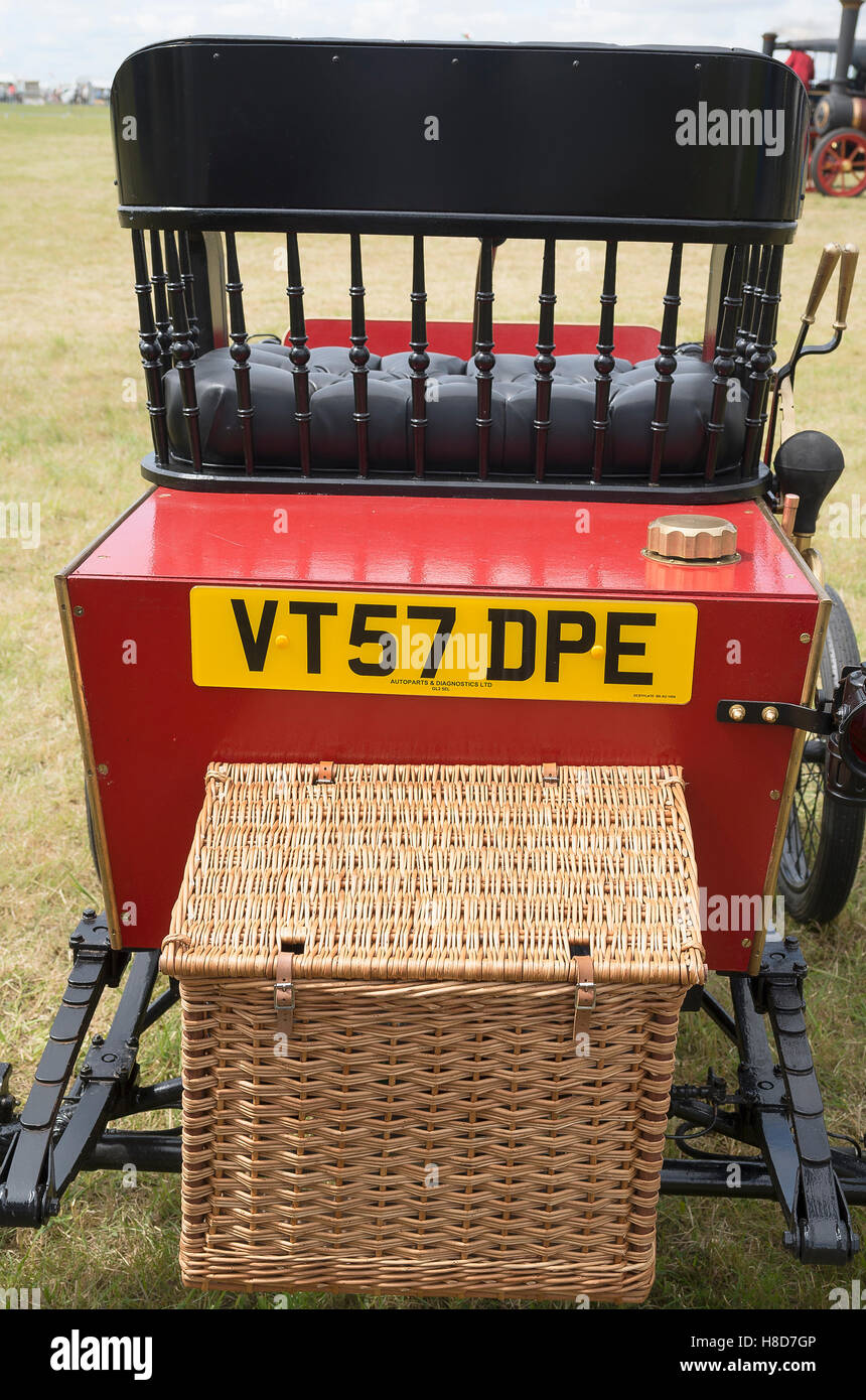 A modern reproduction of a veteran car complete with wicker picnic basket fitted to the rear - Stock Image