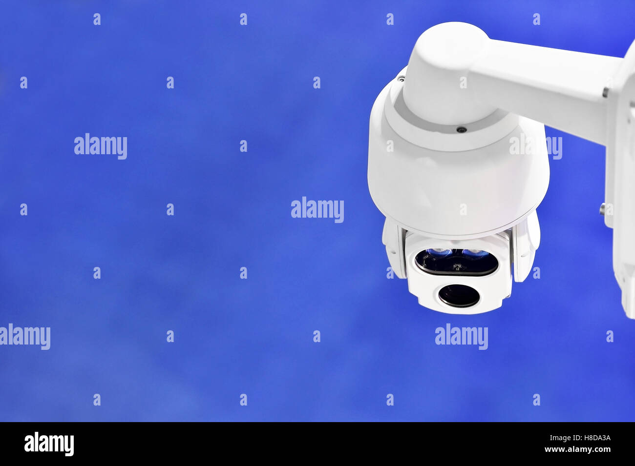 Surveillance camera inside a company with blue background - Stock Image