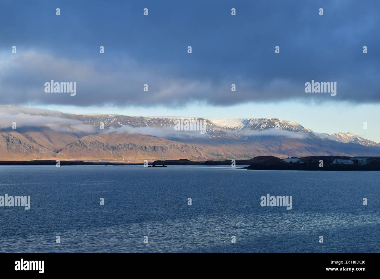on the shore overlooking snowy mountains with cloud cover. - Stock Image