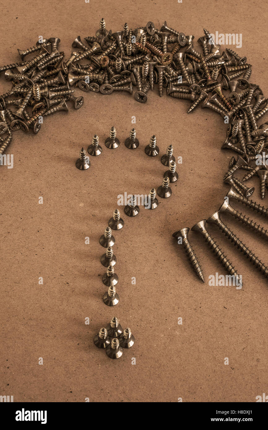 Pile and Line of Screws in shape of Question Mark - Stock Image