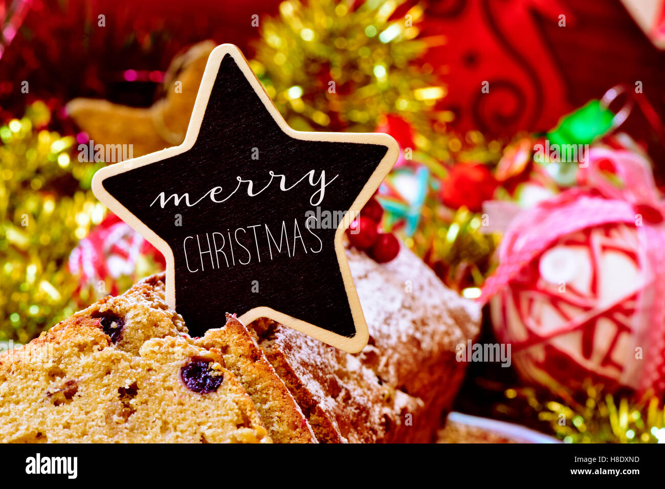 closeup of a fruitcake topped with a star-shaped signboard with the text merry christmas, on a table full of christmas Stock Photo
