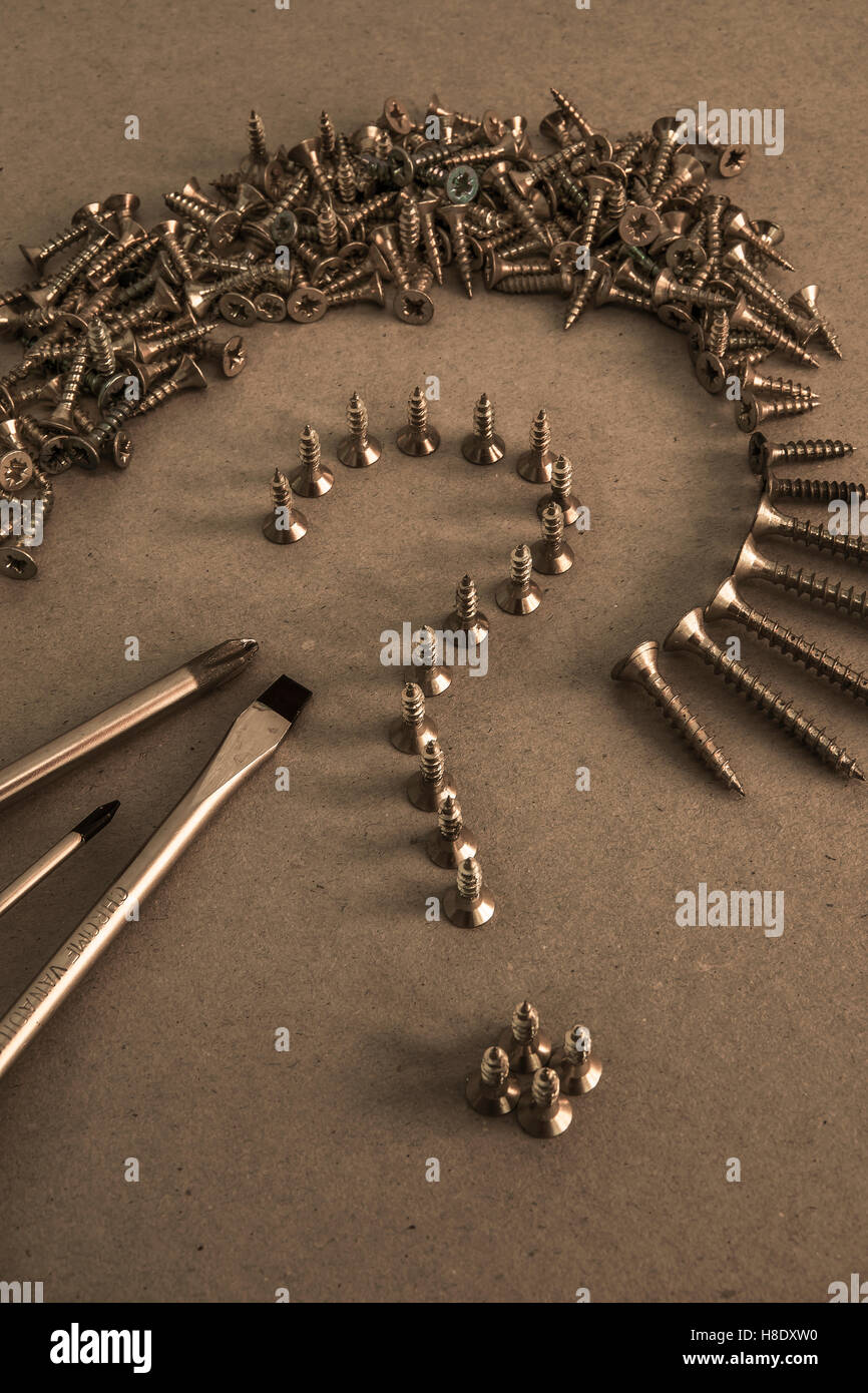 Pile and Line of Screws lin shape of Question Mark with screwdrivers - Stock Image