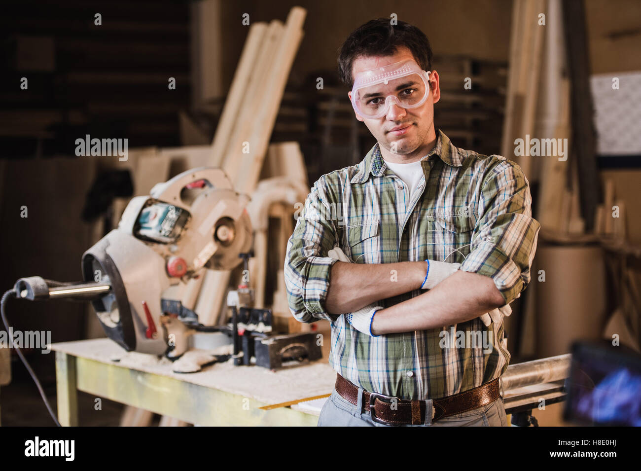 Handsome carpenter in protective glasses is looking at camera and smiling while standing near his wooden object - Stock Image