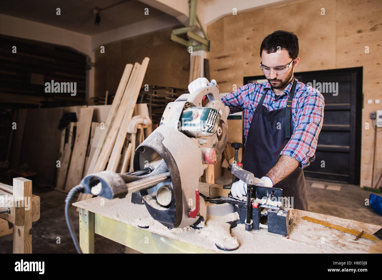Carpenter Using Circular Saw for wood at his workshop - Stock Image