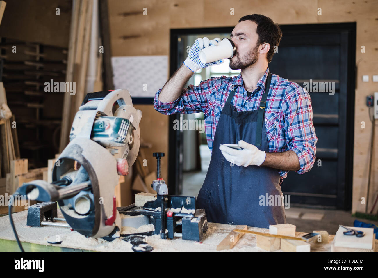 Coffee mug for good work. Thoughtful young male carpenter holding cup while standing near the wooden table with - Stock Image