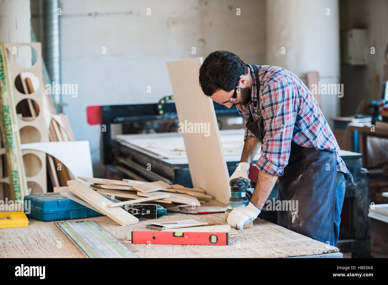 Carpenter with power grinder at his workshop - Stock Image