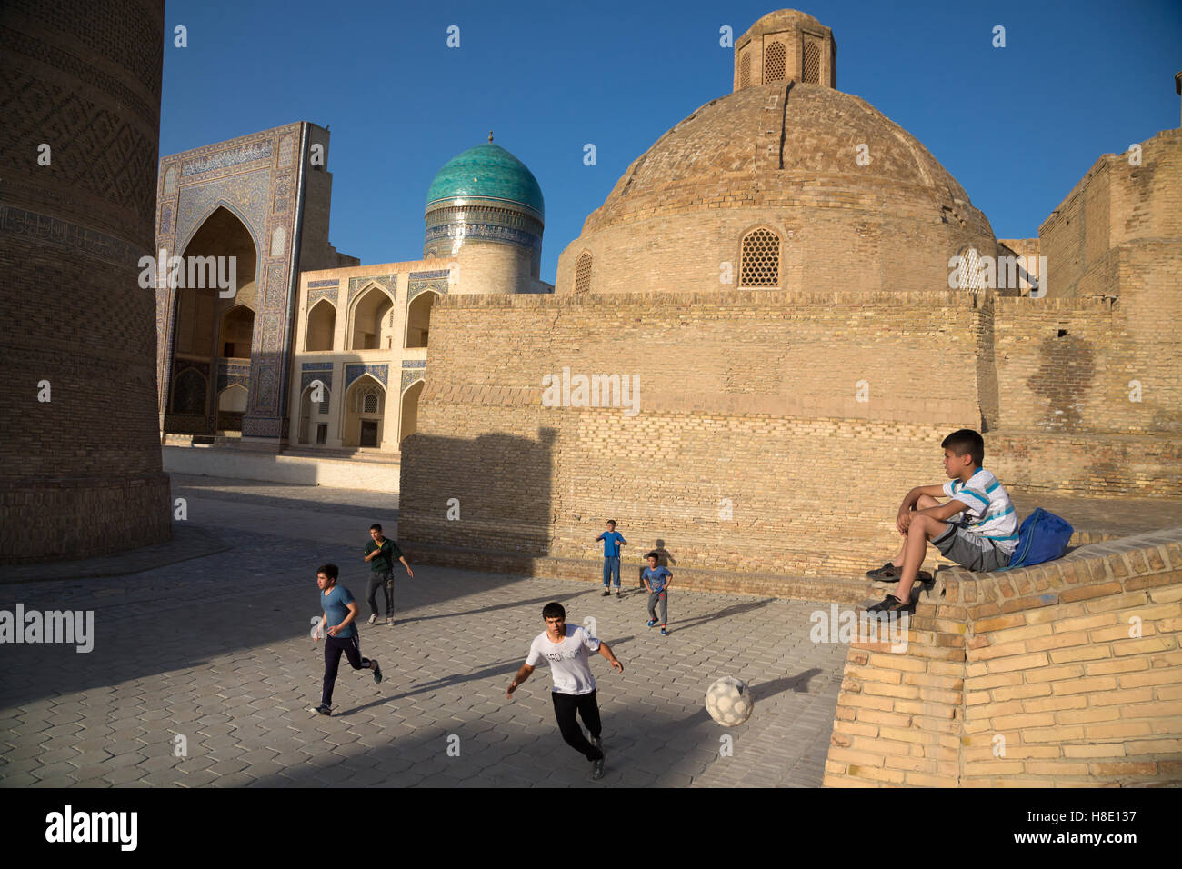 Teenagers kids play football by sunset in antique city Bukhara - Uzbekistan -  travel pictures silk road - Stock Image
