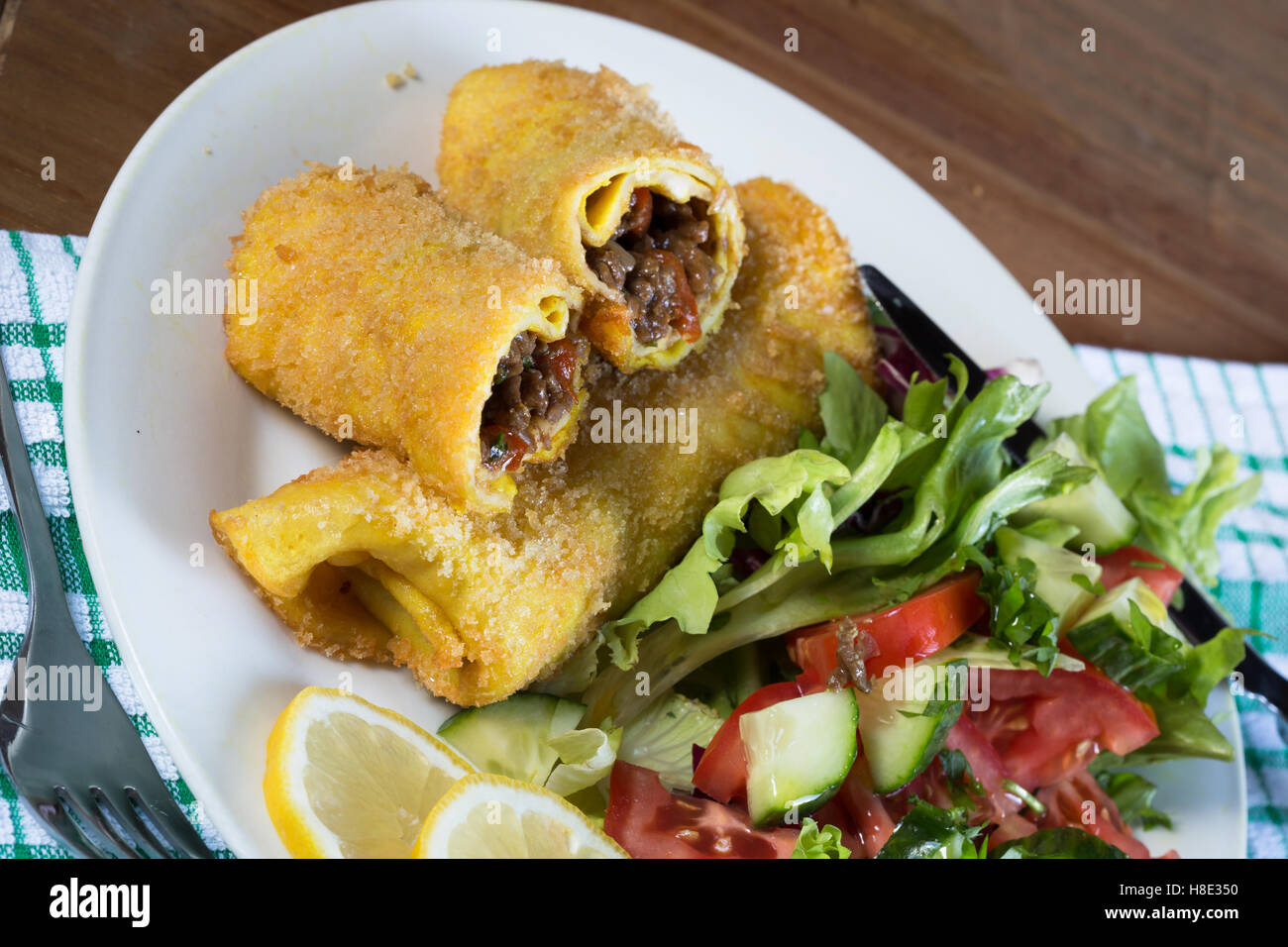 A plated meal of traditional Turkish Hunters Pastry (Avci Boreqi) with a fresh mixed side salad - Stock Image