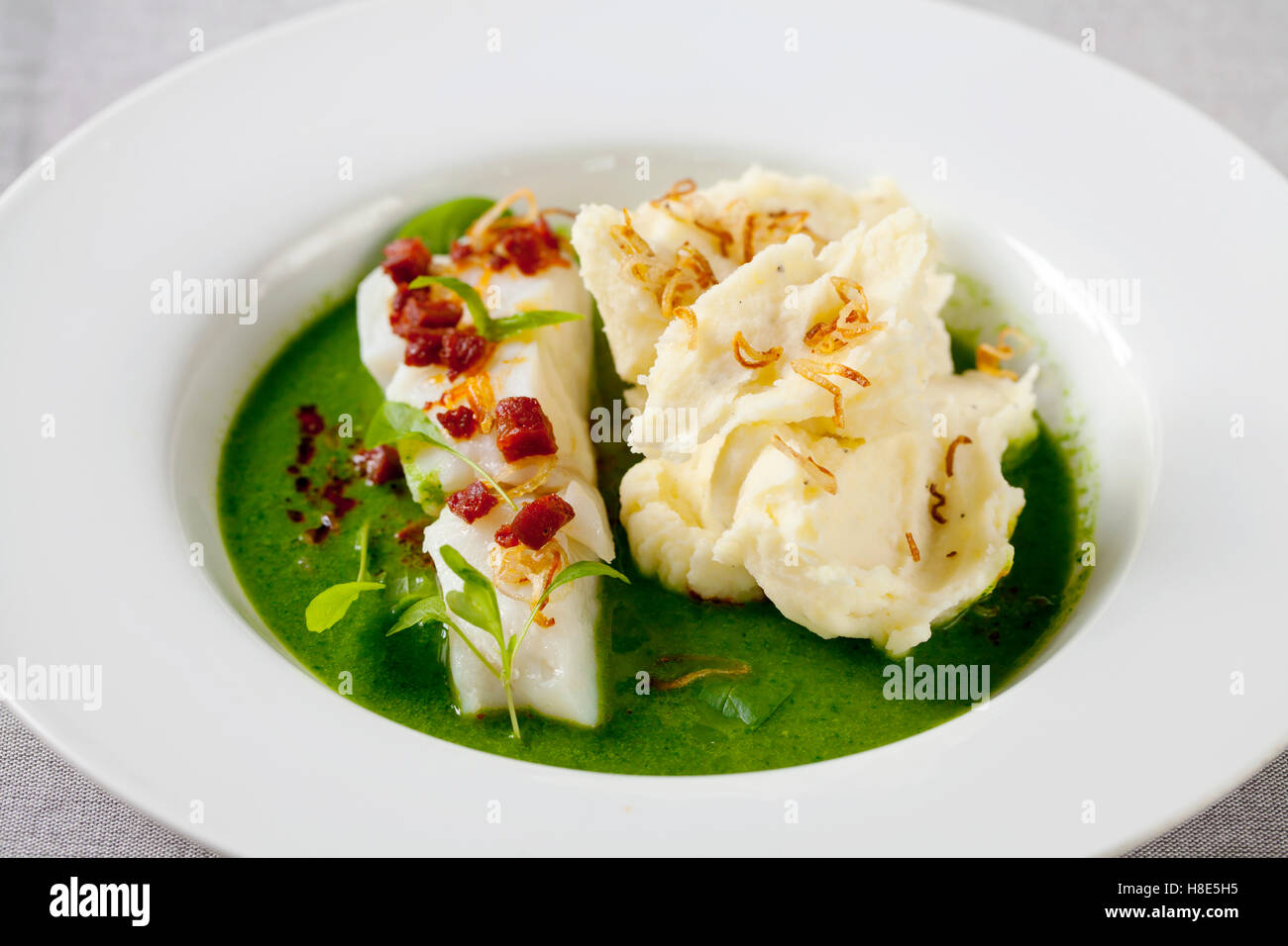 Butter poached cod with green peas, spinach and basil veloute, crispy chorizo and shallots - Stock Image