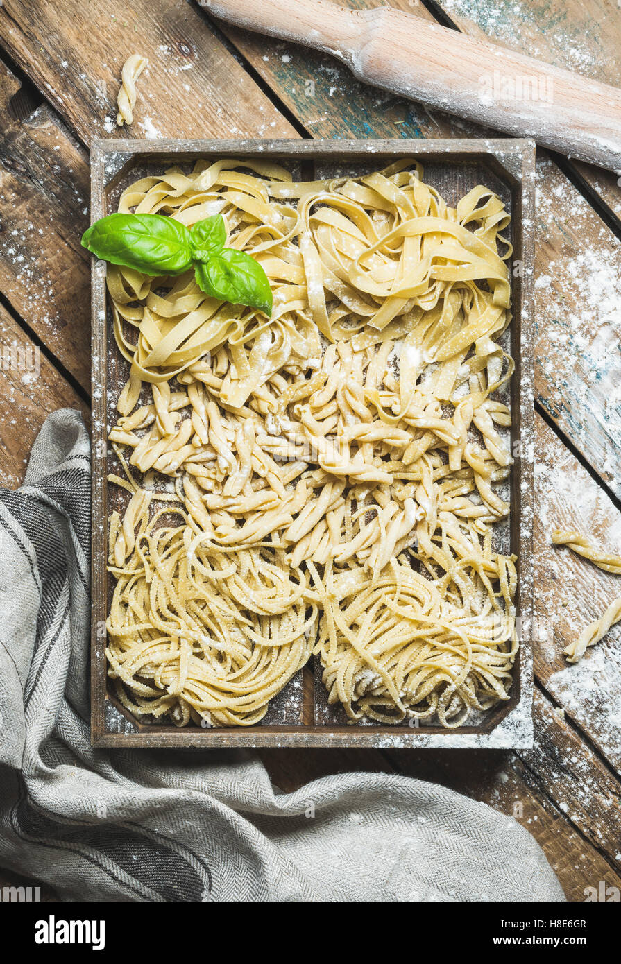 Various homemade fresh uncooked Italian pasta with flour and green basil leaves in wooden tray over shabby background, - Stock Image