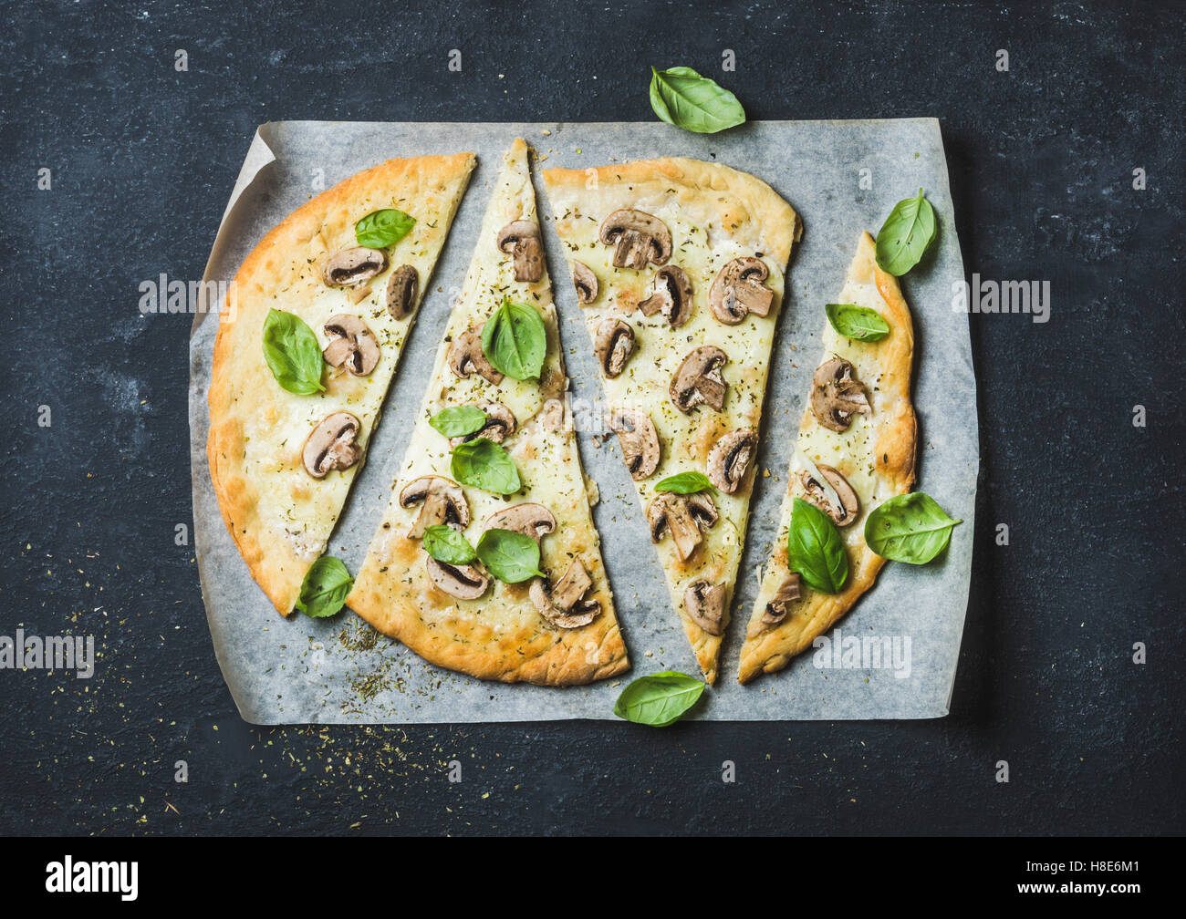Homemade mushroom pizza with basil cut in slices on baking paper over black stone background, top view, horizontal - Stock Image