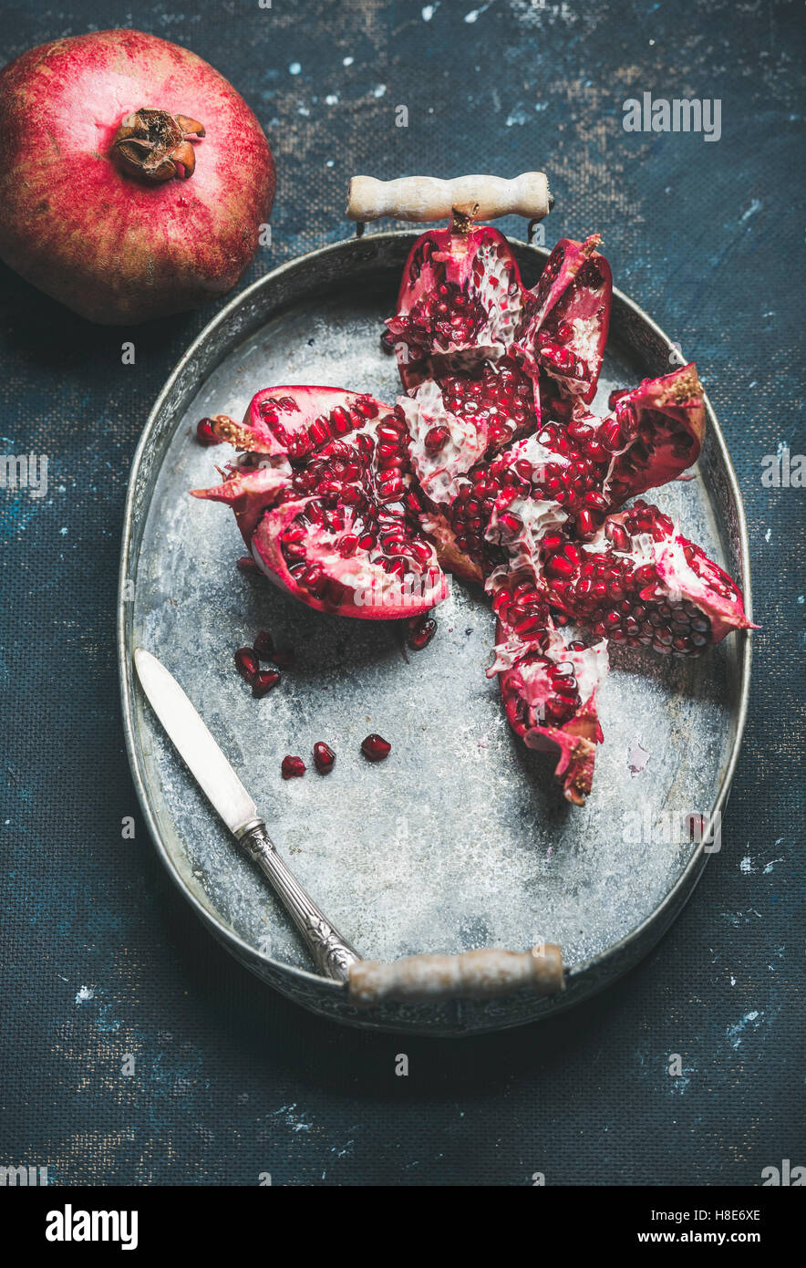 Fresh ripe pomegranate in vintage metal tray over dark blue plywood background, selective focus, copy space, vertical - Stock Image