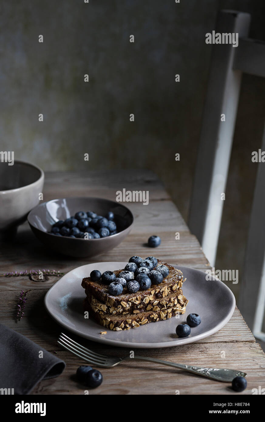 Breakfast with cereal bread and blueberries on wooden table - Stock Image