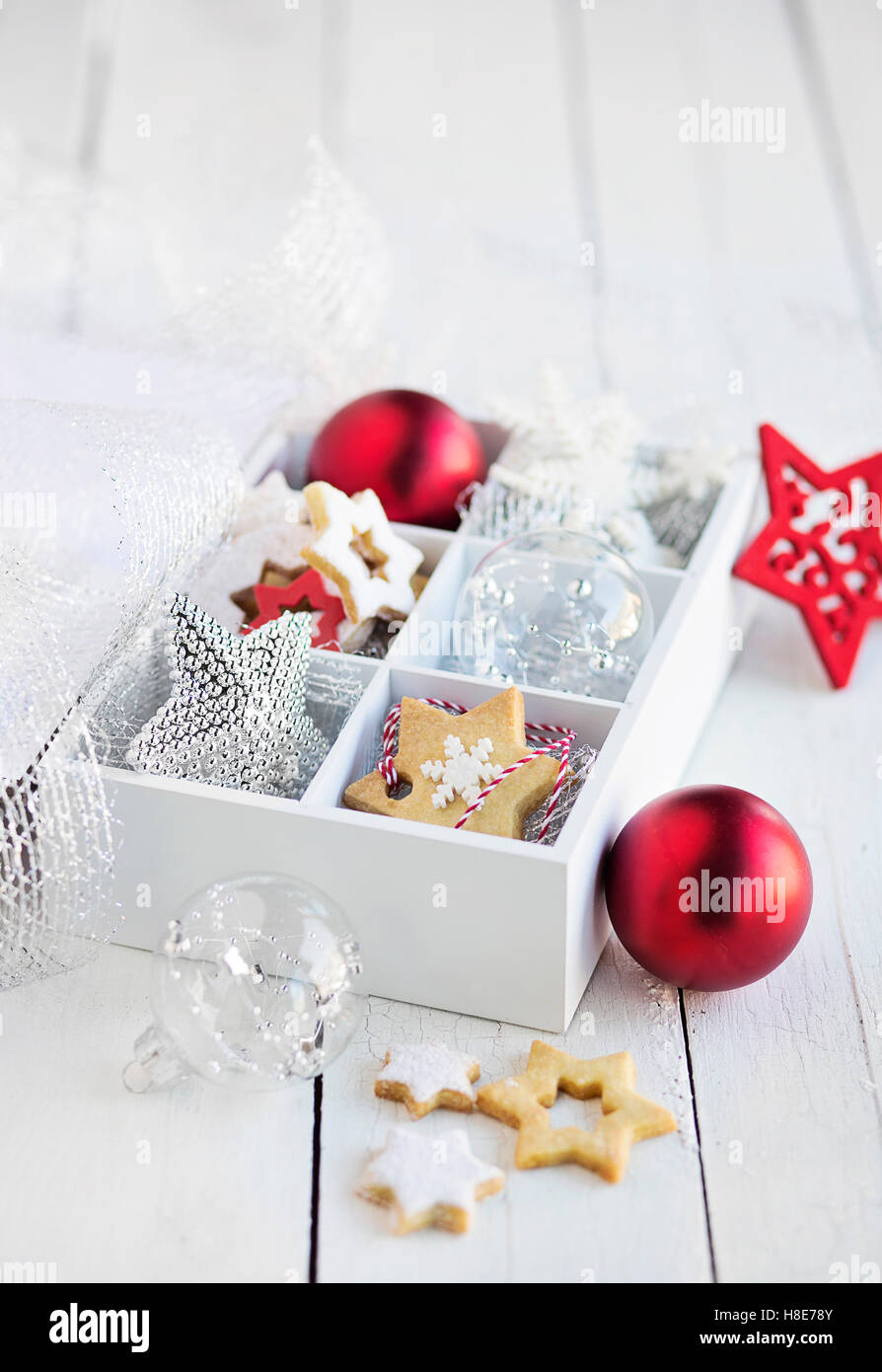 Box with christmas biscuits and decorations on white table - Stock Image