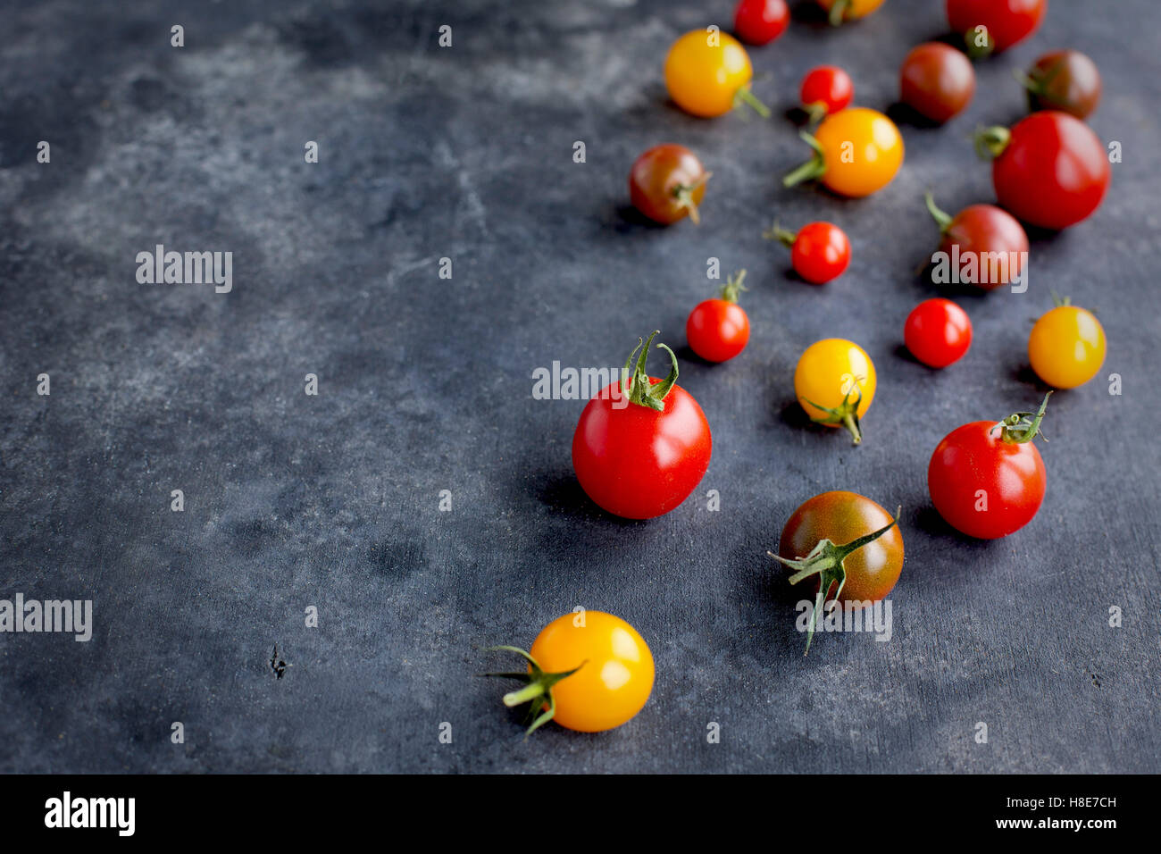 Beige ceramic bowl of cherry tomatoes. Photographed on a black/grey background from front view. - Stock Image