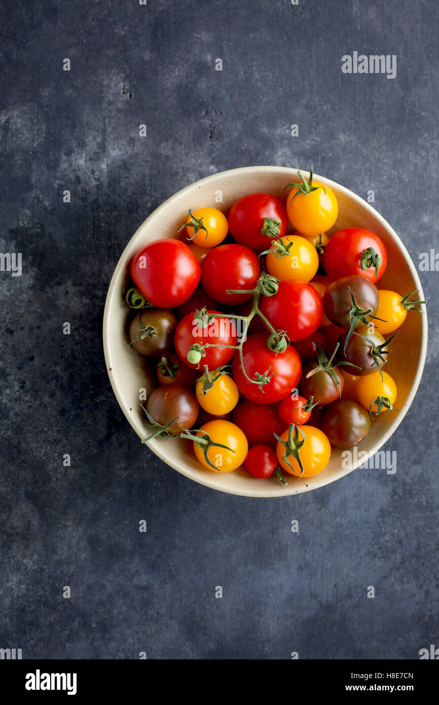 Beige ceramic bowl of cherry tomatoes. Photographed on a black/grey background from top view. - Stock Image