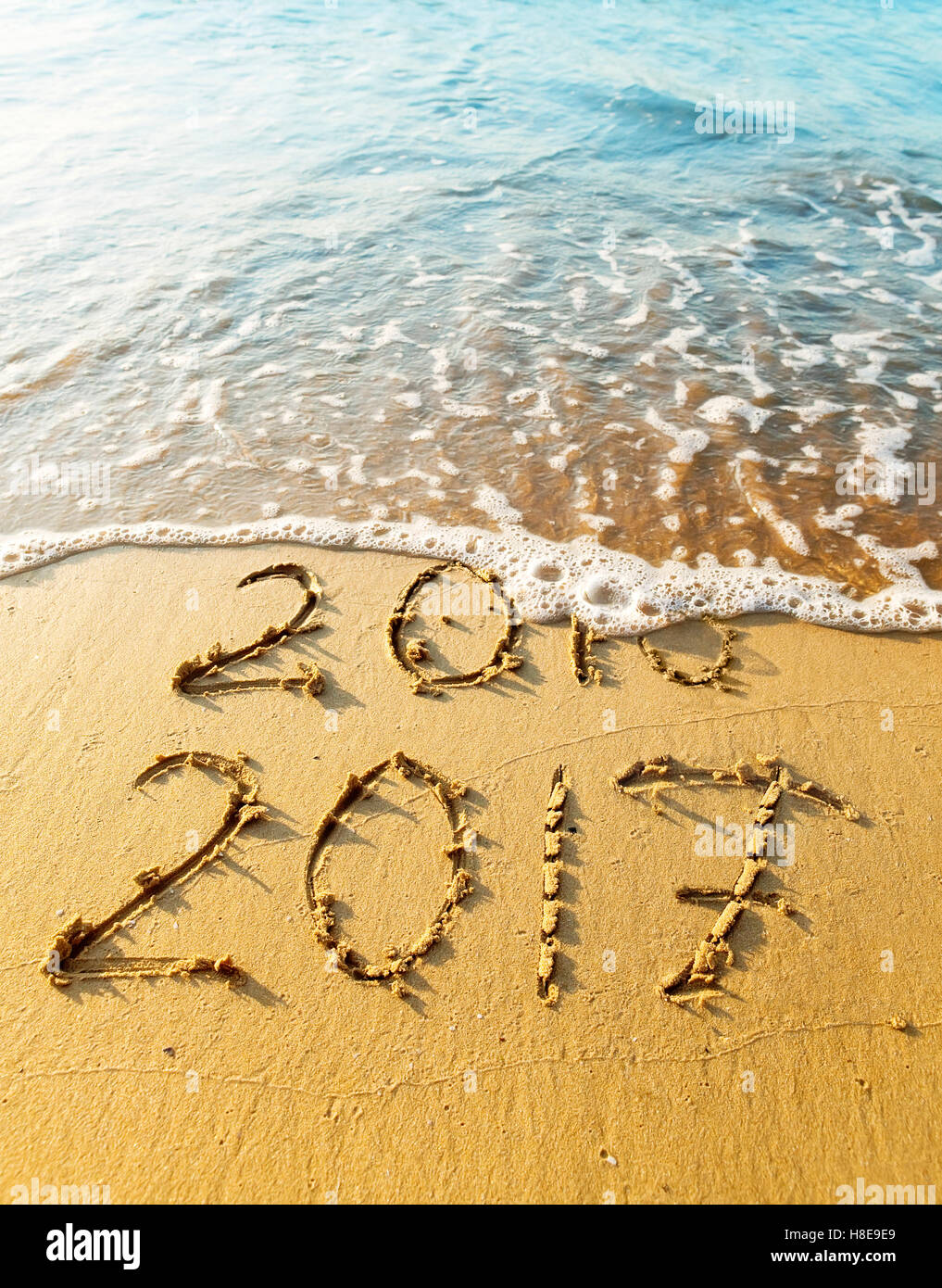 New Year 2017 is coming concept - inscription 2016 and 2017 on a beach sand, the wave is covering digits 2016. - Stock Image