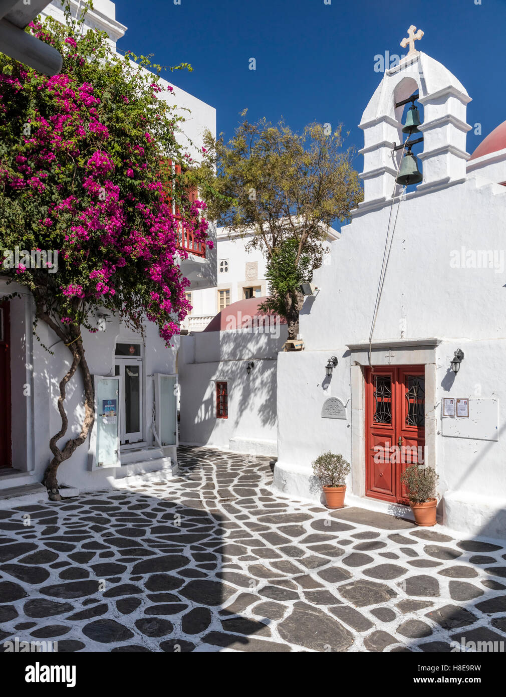Agia Kyriaki Square in Mykonos with bougainvillea, whitewashed walls, and Greek Orthodox church. Cyclades islands, - Stock Image