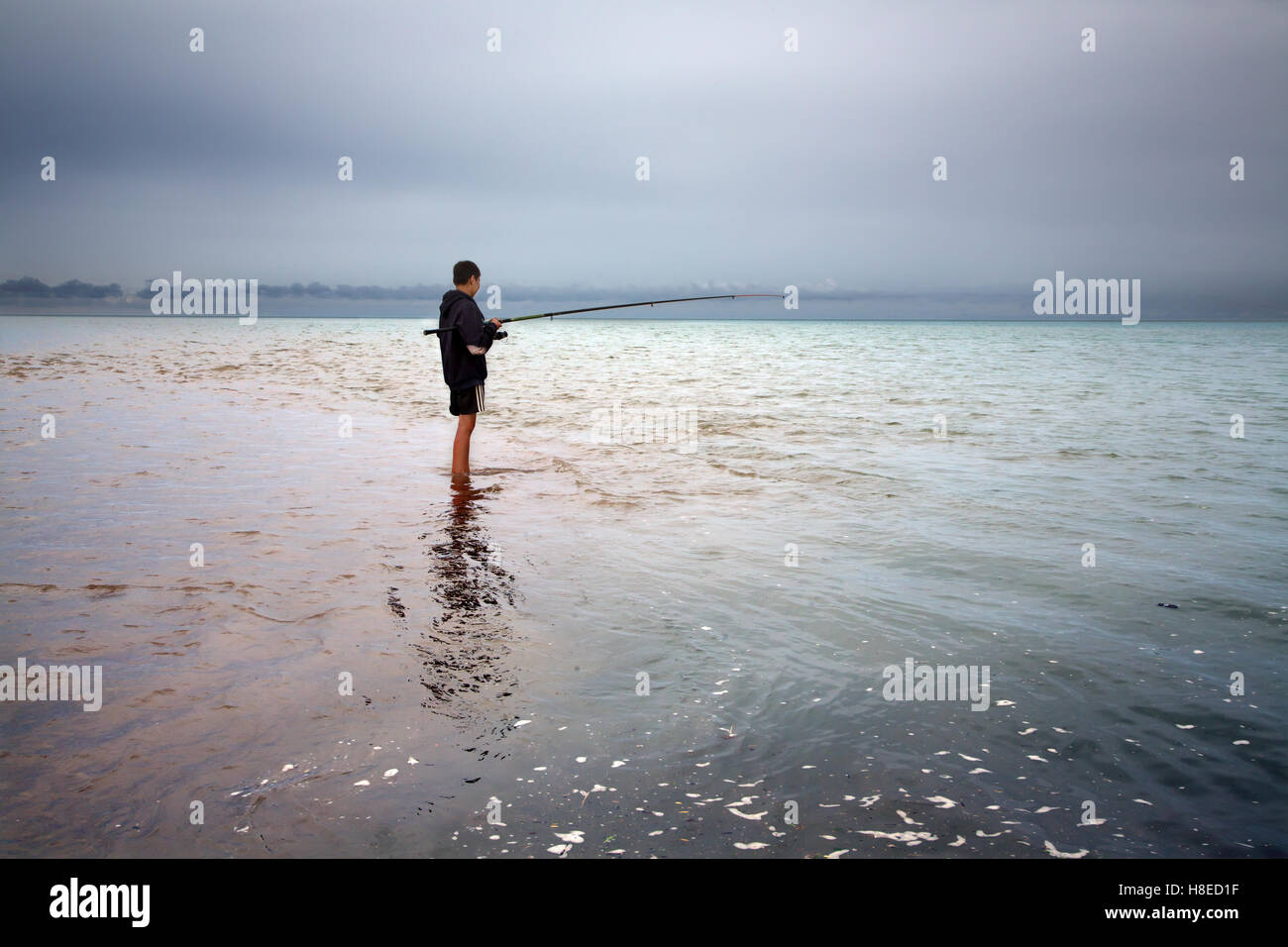 Kyrgyzstan - nomadic child fishing in Issyk-Kul lake  -  Travel people Central Asia - Stock Image