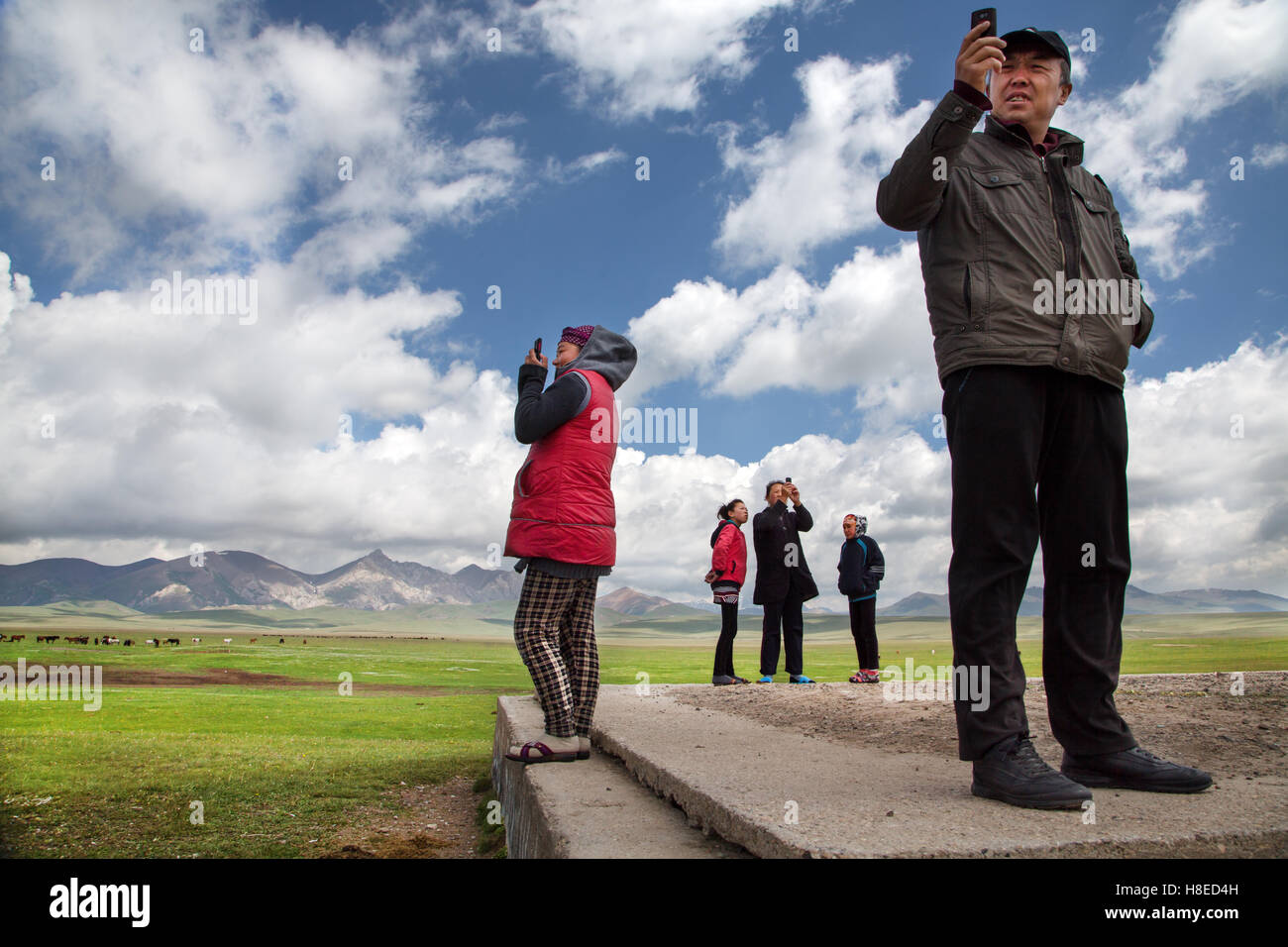 People searching for cell / mobile phone network at Song Kol lake , Kyrgyzstan - Stock Image